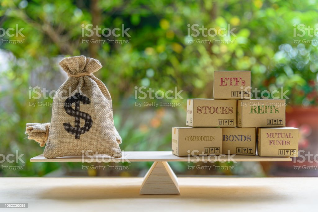 Portfolio management and asset allocation concept : Dollar bag, financial products on balance scale e.g ETFs, REITs, stocks, commodities, bonds, mutual funds, depicts balancing between risk and return stock photo