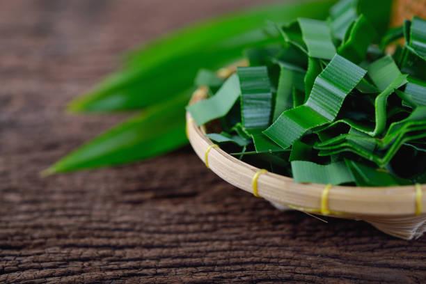 portion cut pandan leaves in bamboo basket and on wooden table - pandan składnik zdjęcia i obrazy z banku zdjęć