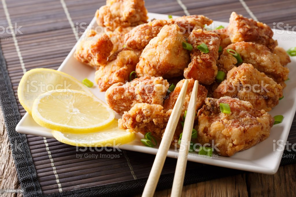 Portion fried chicken karaage with lemon and onion close-up on a plate. horizontal stock photo