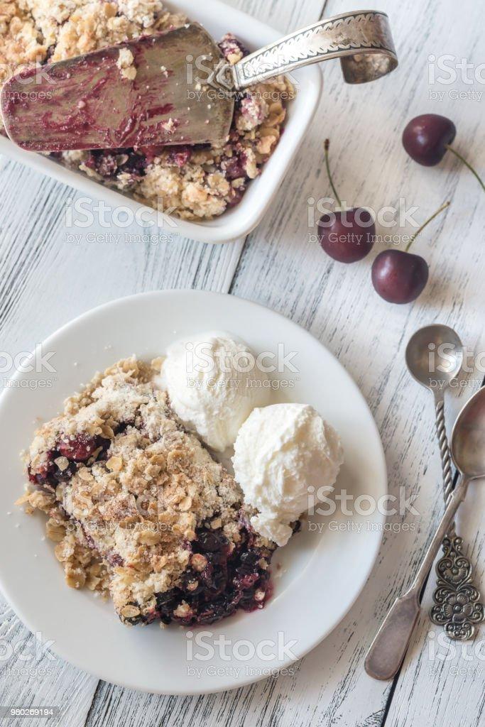 Portion of berry crumble with vanilla ice cream stock photo
