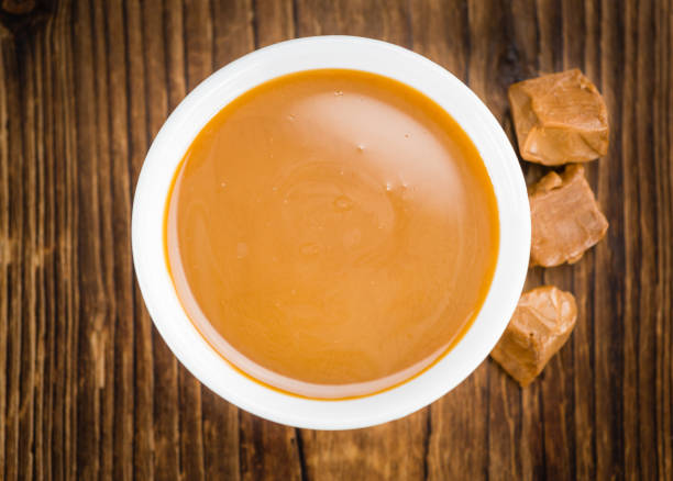 portion karamell sauce auf hölzernen hintergrund (tiefenschärfe) - karamellsirup stock-fotos und bilder