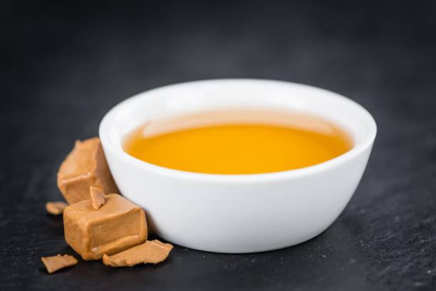 portion karamell-sirup auf einer schiefertafel tafel - karamellsirup stock-fotos und bilder