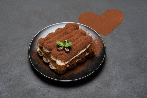 portion of Classic tiramisu dessert on ceramic plate and heart shaped cocoa powder on concrete background stock photo