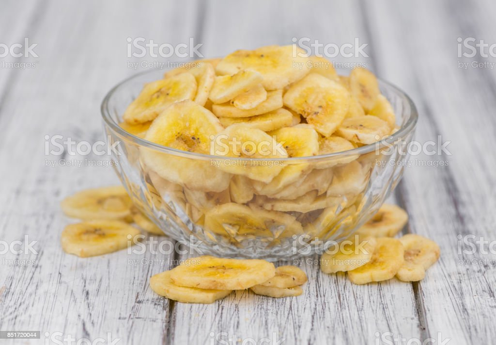 Portion of Dried Banana Chips on wooden background, selective focus stock photo