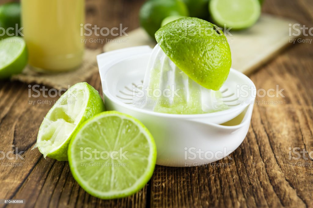 Portion of Fresh Lime Juice on wooden background (selective focus) stock photo