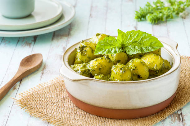 Portion of gnocchi with 'Pesto' sauce, in terracotta bowl. - foto stock