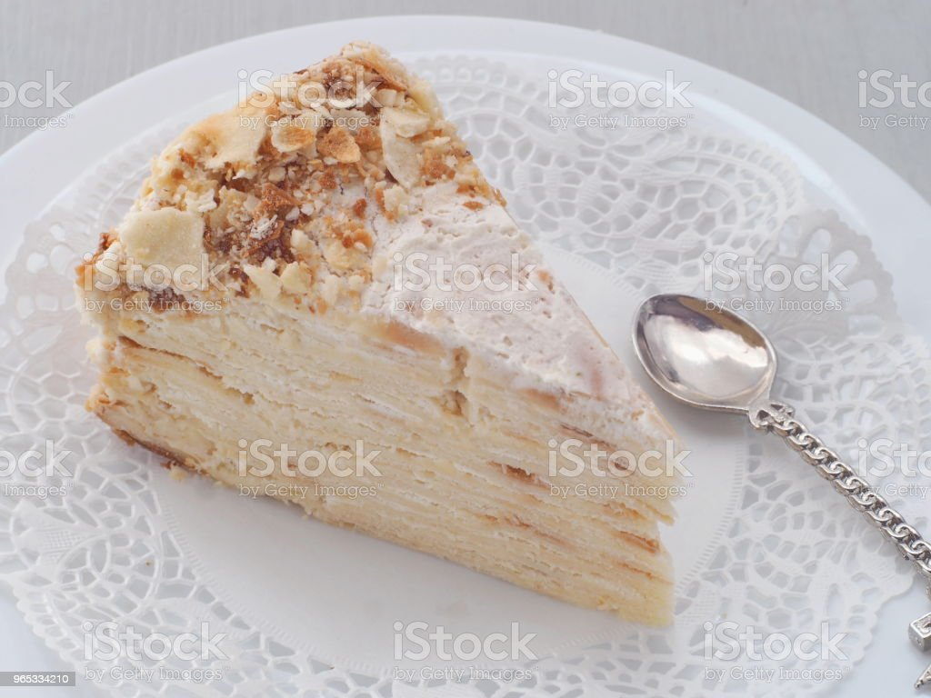 Portion of multi layered cake upon white plate. Puff pastry cake decorated with crumbs. zbiór zdjęć royalty-free