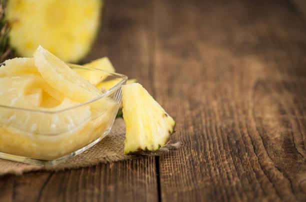 teil des erhaltenen ananasringe auf hölzernen hintergrund, selektiven fokus - ananas marmelade stock-fotos und bilder
