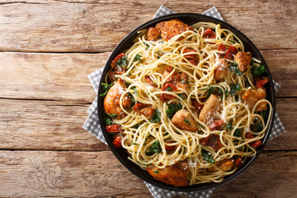 Portion of spaghetti with dried tomatoes, sliced chicken, Parmesan and spinach, close-up on a plate. Horizontal top view stock photo