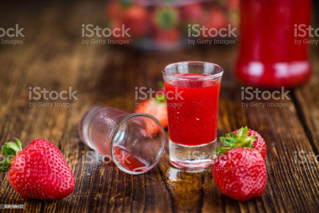 Portion of Strawberry liqueur on wooden background, selective focus stock photo