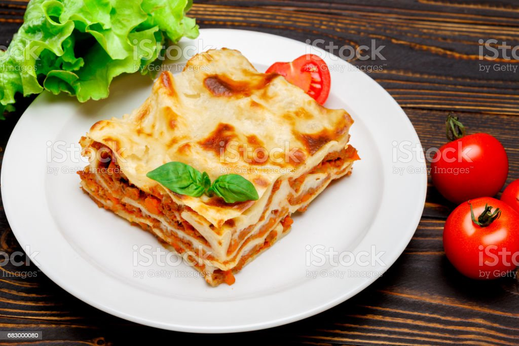 Portion of tasty lasagna on wooden backgound royalty-free stock photo