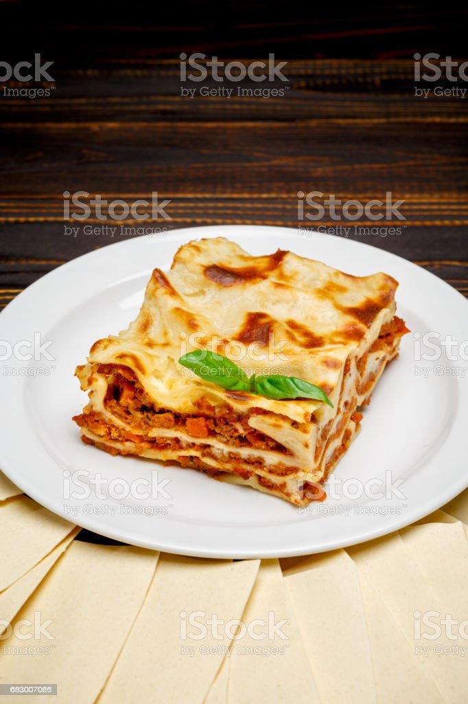 Portion of tasty lasagna on wooden backgound foto de stock royalty-free