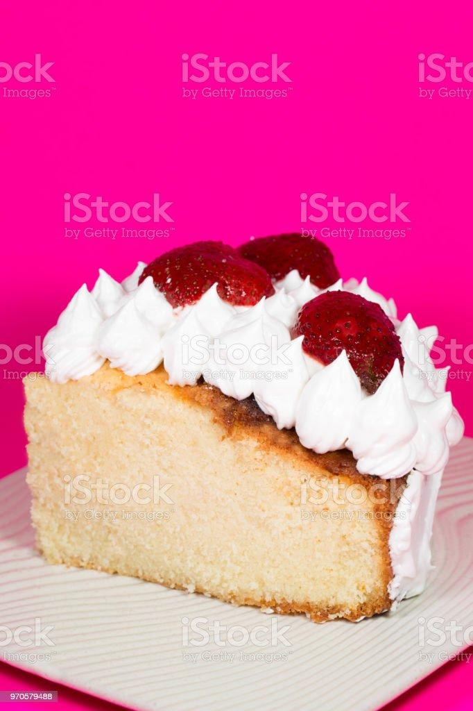 Gedeelte van vanille Cake gegarneerd met aardbeien en room over Magenta foto