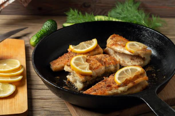 Portionierte Stücke gebratenen Fischs in einer schwarzen gusseisernen Pfanne mit frischen Gurken und Kräutern. Traditionelles Abendessen eines Dorffischers – Foto