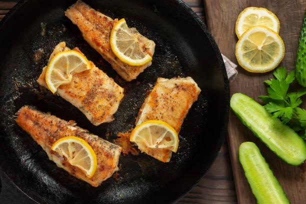 Portionierte Stücke gebratenen Fischs in einer schwarzen gusseisernen Pfanne mit frischen Gurken und Kräutern. Traditionelles Abendessen eines Dorffischers, Ansicht von oben, flache Lage – Foto
