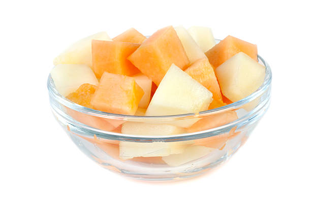 Portions of melons in glass bowl stock photo