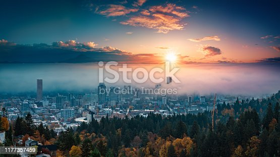A photograph of Portland downtown with rolling fog and autumn foliage in shining sunrise and colorful clouds