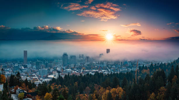 Portland downtown with rolling fog and autumn foliage in shining sunrise and colorful clouds stock photo