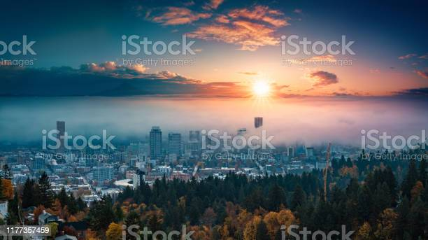 Photo of Portland downtown with rolling fog and autumn foliage in shining sunrise and colorful clouds