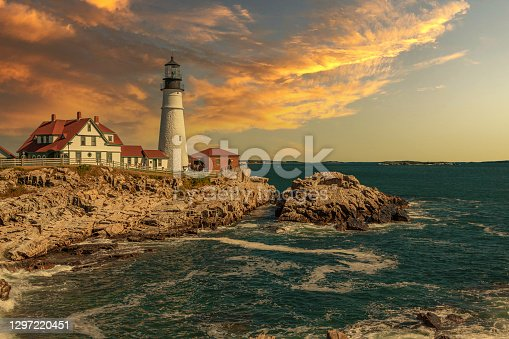 Portland Head Lighthouse, Cape Elizabeth, Maine, lit by the Morning Sun. Rocky Coastline with Cliffs, Ocean Surf and Blue Sky are in the image.