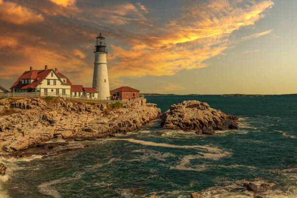 Portland Head Light with Rocky Cliffs, Ocean Surf and Beautiful Sunset Sky. stock photo