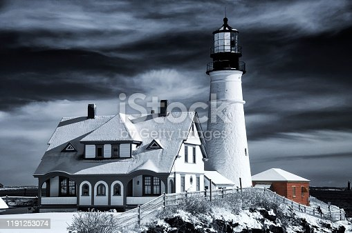 A black and white photo of the iconic landmark Portland Headlight after a winter storm in Portland Maine.