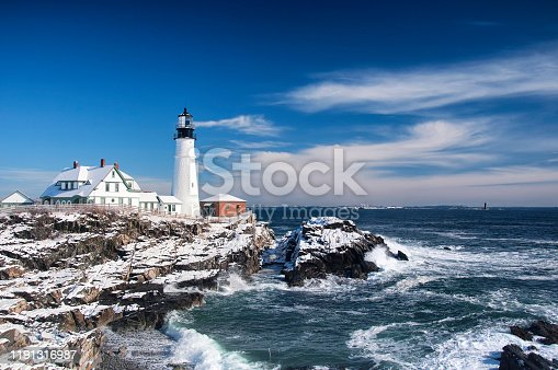 the iconic landmark Portland Headlight after a winter storm in Portland Maine on a sunny blue sky day.