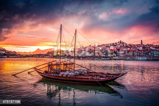 Porto at Sunset with Rabelo Boats on Douro River and the city in the background. The sky is coloured and the boats are in the foreground.