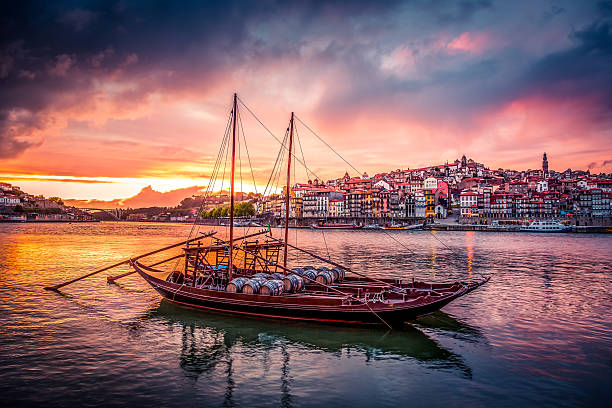 Porto at Sunset with Rabelo Boats on Douro River Porto at Sunset with Rabelo Boats on Douro River and the city in the background. The sky is coloured and the boats are in the foreground. duero stock pictures, royalty-free photos & images