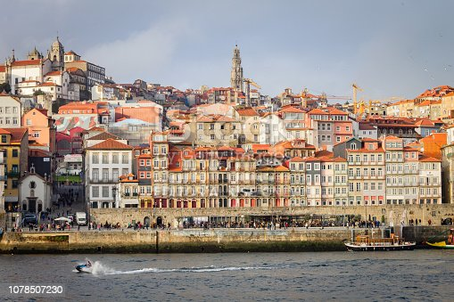 Porto, Portugal - November 28, 2018: Ceramic tile facades and historic buildings at the Ribeira, in Porto, Portugal, against a cloudy sky background, while a speedboat speeds along the Douro River.