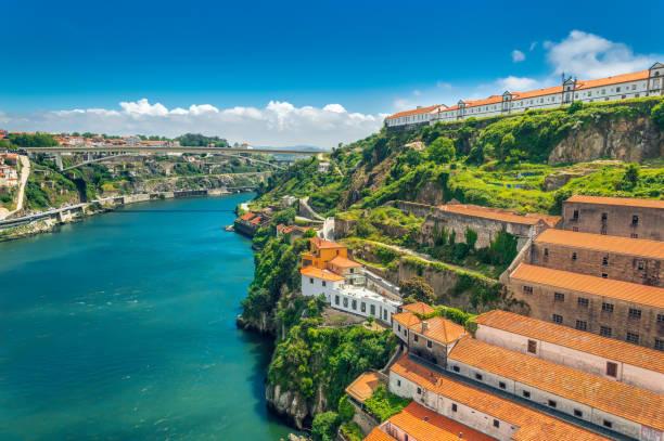 porto, portugal: heuvels van vila nova de gaia en wijnkelders over rivier duero - portugal stockfoto's en -beelden