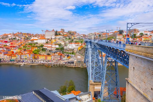 Porto, Portugal - April 1, 2018: Old town ribeira aerial promenade view with colorful houses, Douro river and Luis I bridge