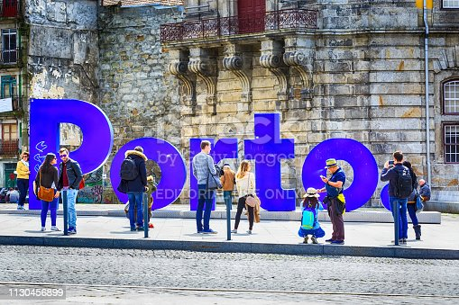 Porto, Portugal -April 1, 2018: Old town street view with Porto city name sign and people