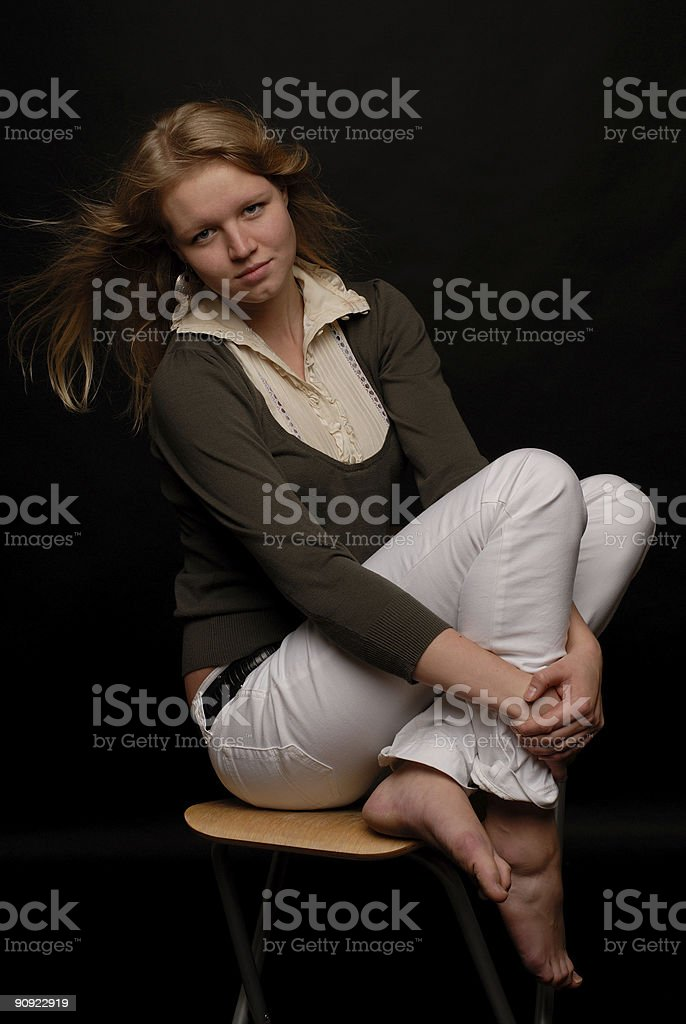 Portrail of blond girl on chair knees to her chin royalty-free stock photo