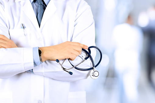istock Portrait an unknown male doctor holding a stethoscope behind 517051420