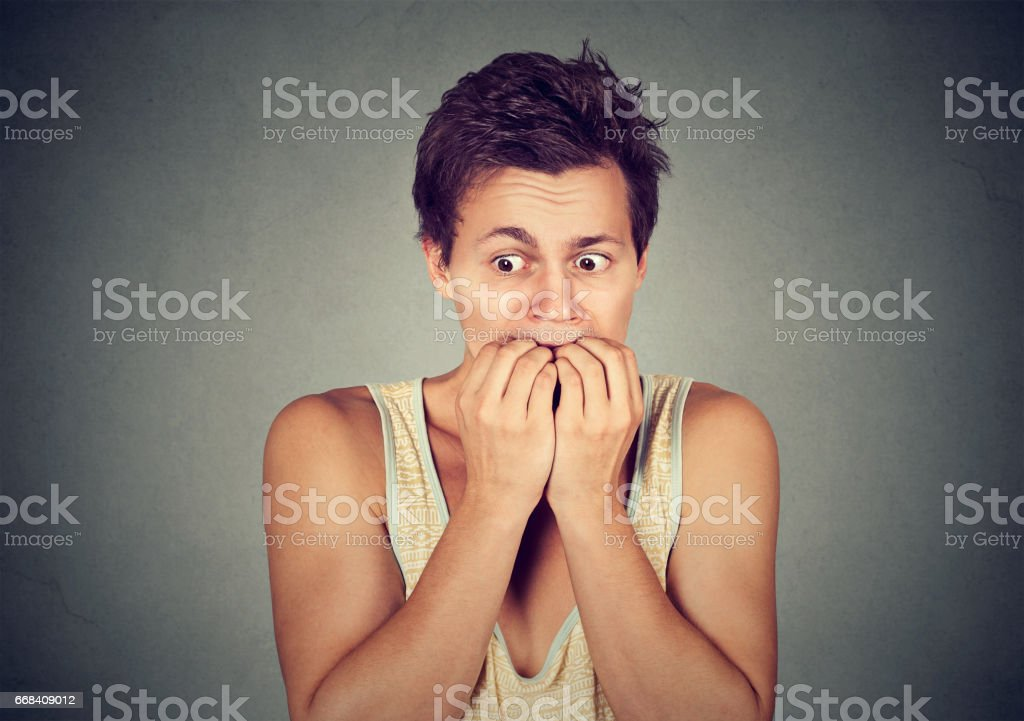 Portrait anxious young man biting his nails fingers freaking out stock photo