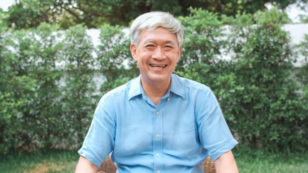 Porträt asiatische chinesische Senior Mann das Gefühl glücklich lächelnd zu Hause. Ältere Männliche entspannen zu schüchtern Lächeln blickend in die Kamera, während im Garten zu Hause im MorgenKonzept liegen. – Foto