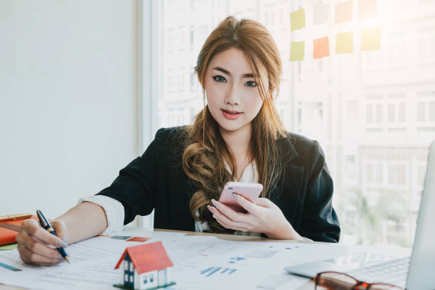 Portrait asian real estate agent singing contract with home model at modern office. business concept about real estate market stock photo