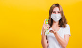 istock Portrait Asian Thai beautiful young woman wear mask protection clean corona virus on hand with alcohol gel or antibacterial soap sanitizer, studio shot isolated 1215713278