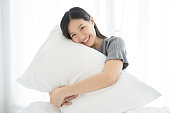 Portrait Asian woman and pillow wake up on bed at home