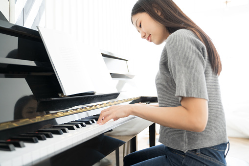 Portrait Asian woman playing  playing piano
