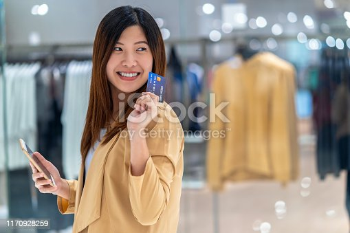 508915178istockphoto Portrait Asian woman using credit card with smart mobile phone for online shopping in department store over the clothes shop store background, technology money wallet and online payment concept 1170928259