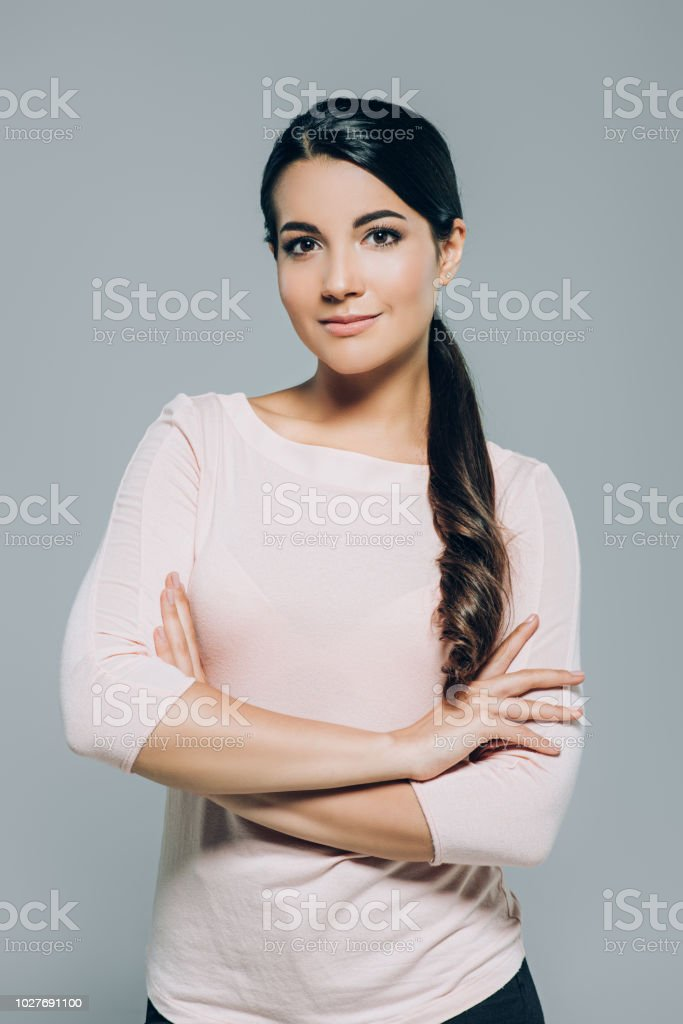 portrait attractive brunette woman with arms crossed posing isolated...