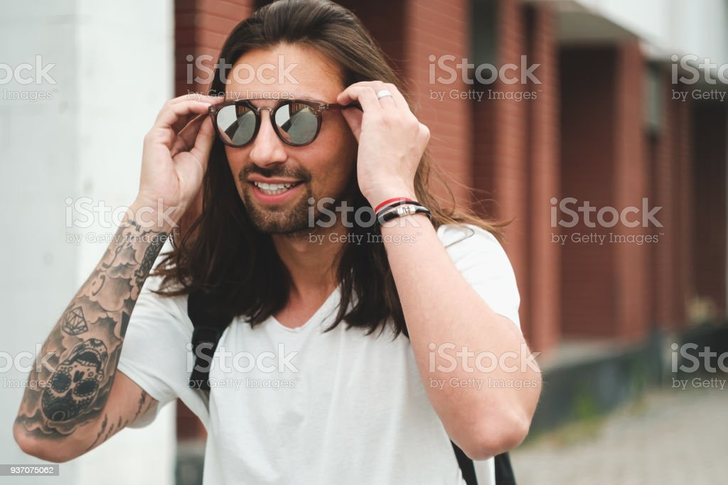 Portrait attractive man with sunglasses on urban background smil stock photo