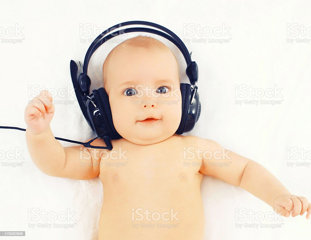 Portrait baby listens to music in headphones lying stock photo