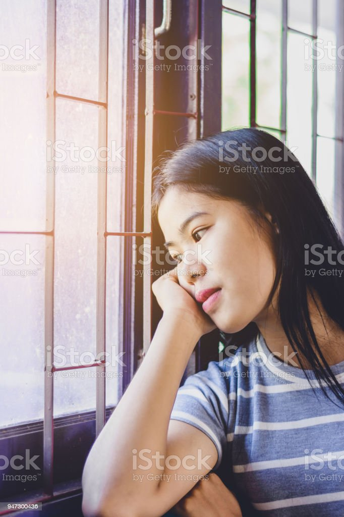 Portrait  beautiful Asian woman, depress and looking out the window at sunset stock photo