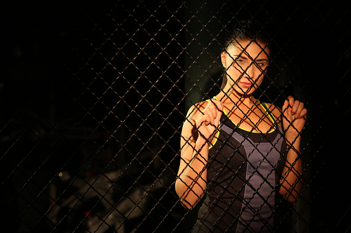 629605142 istock photo Portrait beautiful fitness girl near fence of grid in gym 502814470