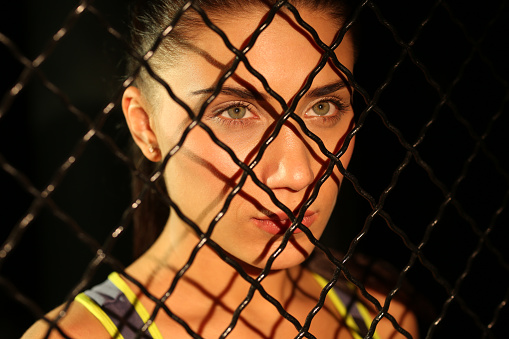629605142 istock photo Portrait beautiful fitness girl near fence of grid in gym 502814488