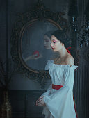 istock Portrait beautiful woman concept sleeping beauty horror dream. fairytale medieval clothes dress. Gothic girl princess makeup red lips. Ghost female hand with poison apple is reflected vintage mirror 1215333703