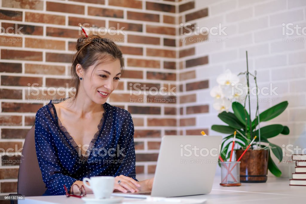 Portrait beautiful woman in office looking to laptop zbiór zdjęć royalty-free